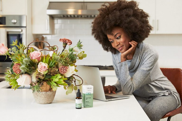 woman looking at computer in home office with Tikva CBD Tincture Oil