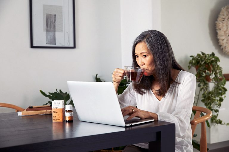 Woman with laptop sipping tea